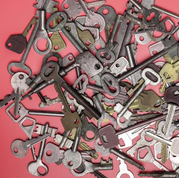 Ключи на розовом фоне. ключи от дверных замков и сейфы для безопасности имущества и охраны дома Premium Фотографии