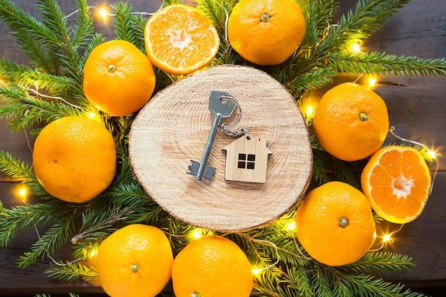Ключи от нового дома на круглом срезе дерева мандаринами, живыми еловыми ветками и гирляндами. передача, доли ипотеки, аренда коттеджа. Premium Фотографии