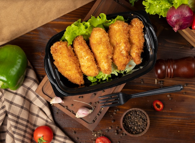 Kfc style fried chicken nuggets takeaway in black container Free Photo