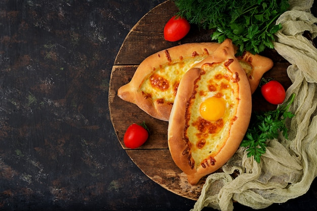 Хачапури по-аджарски. открытый пирог с моцареллой и яйцом. грузинская кухня. Бесплатные Фотографии