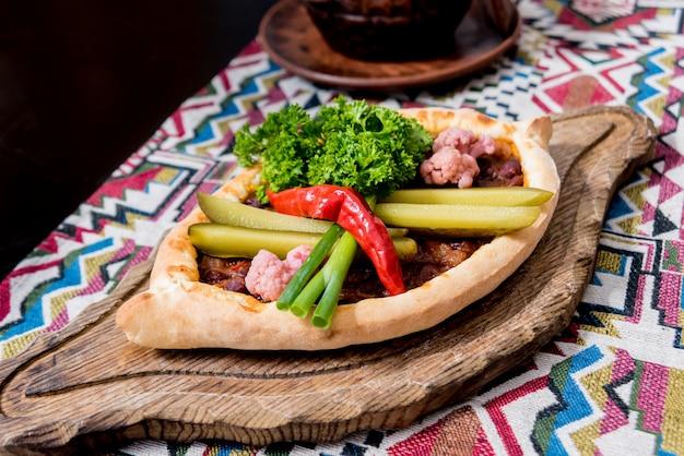 ハチャプリとチーズ、野菜、卵。グルジアの郷土料理。飲食店。 Premium写真