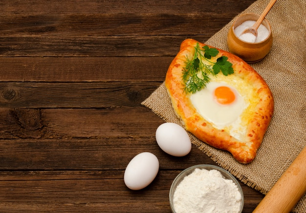 Khachapuri with eggs on sackcloth, salt, flour and eggs. georgian cuisine Premium Photo