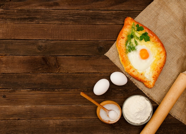 Khachapuri with eggs on sackcloth, salt, flour, eggs and parsley on the wooden table Premium Photo