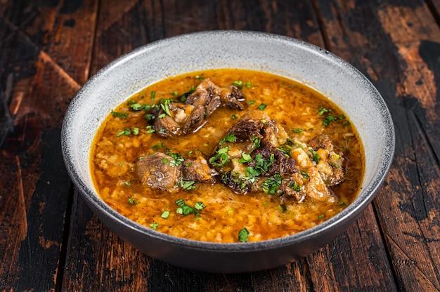 Суп харчо из говядины с рисом, помидорами и специями в миске. темное дерево Premium Фотографии