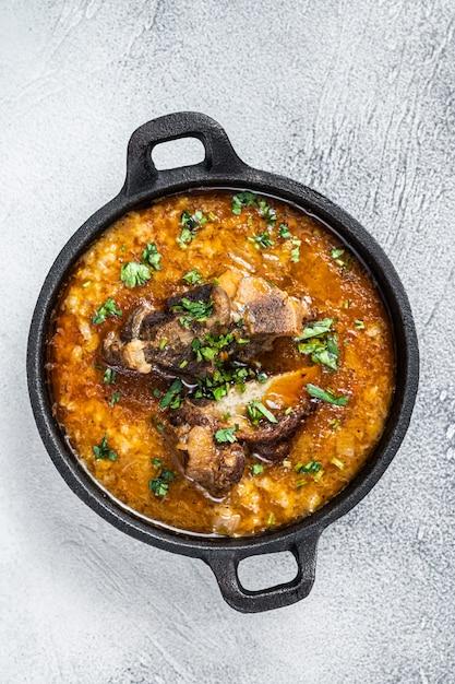 Суп харчо с говядиной, рисом, помидорами и специями на сковороде. белый Premium Фотографии