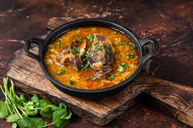 Суп харчо с бараниной, рисом, помидорами, морковью, перцем, грецкими орехами и специями. тьма Premium Фотографии