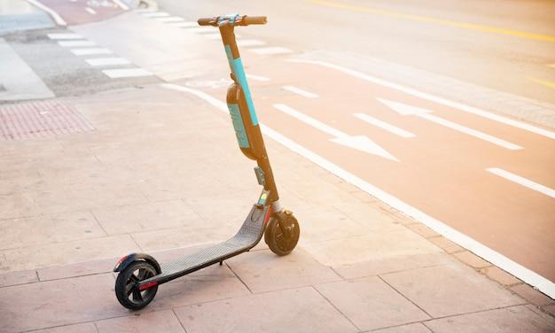 Kick scooter on sidewalk near the cycle lane Free Photo
