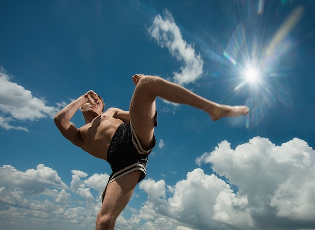 Kickboxer kicks in the open air in summer against the sea. Premium Photo