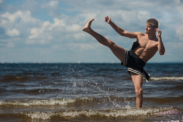 Kickboxer kicks in the open air in summer against the sea Premium Photo