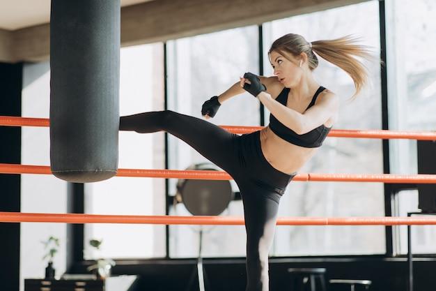 Kickboxing женщина тренировки боксерская груша в фитнес свирепой форме тела Premium Фотографии