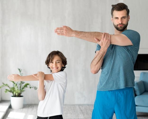 Малыш и его отец занимаются спортом дома Бесплатные Фотографии