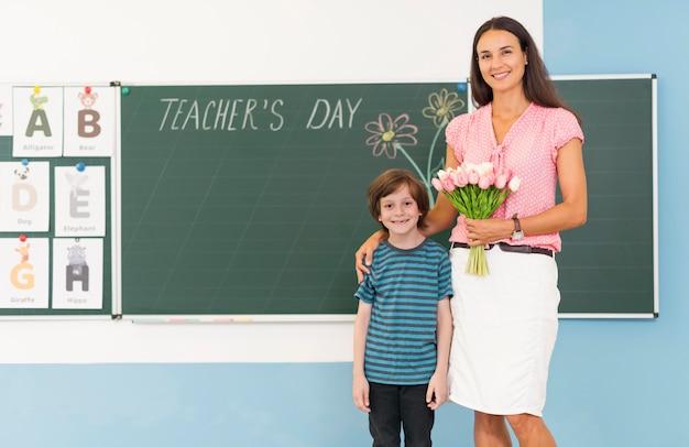 Ребенок и учитель, держа букет цветов с копией пространства Бесплатные Фотографии