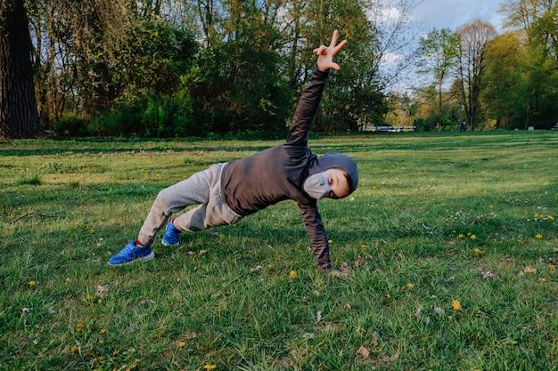 Малыш, одетый как ниндзя, делает разные упражнения на свежем воздухе Premium Фотографии