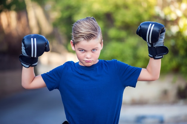 Kid boy with boxing gloves showing strong outdoor Premium Photo