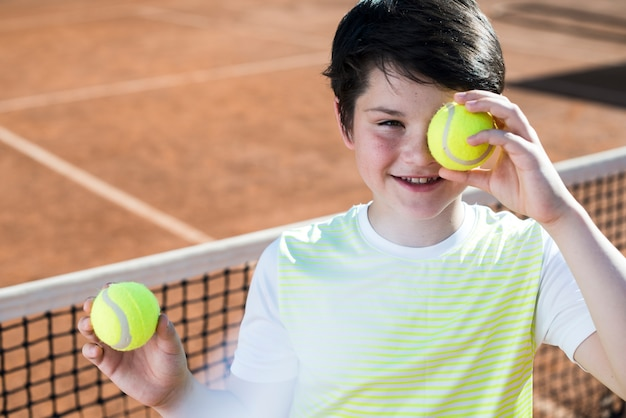 Kid covering his eye with a tennis ball Free Photo