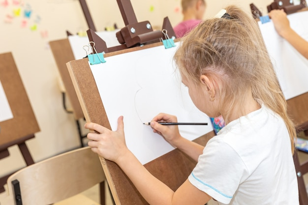 Kid drawing image on easel in classroom Premium Photo