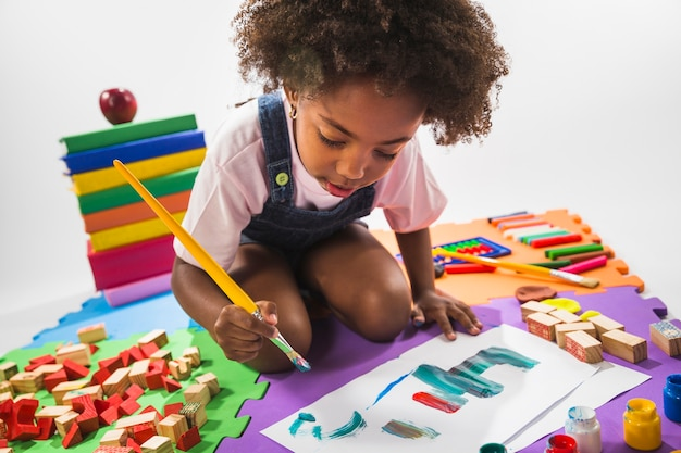Kid drawing on play mat in studio  Free Photo