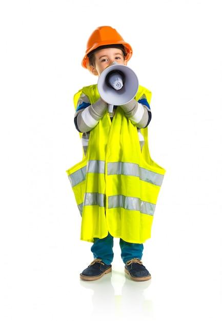 Kid dressed like workman shouting by megaphone Premium Photo
