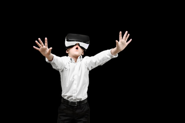 Kid in formal outfit wearing vr glasses putting hands out in excitement isolated Premium Photo