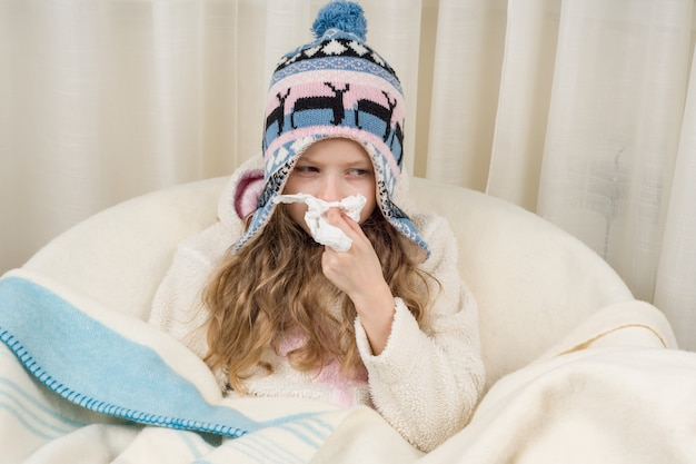 Kid girl sneezes in a handkerchief at home Premium Photo