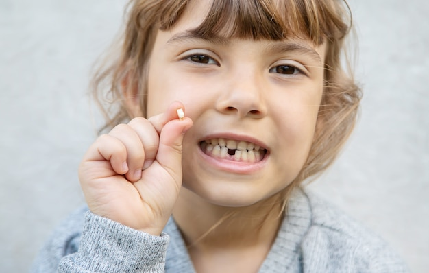 The kid had a baby tooth. Premium Photo