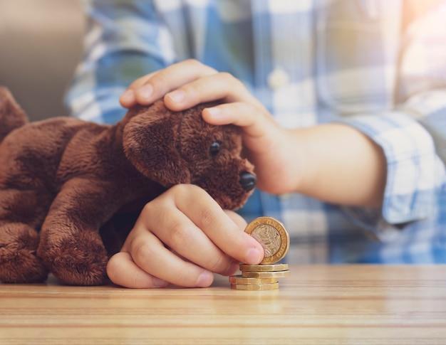 Оягнитесь рука штабелируя и подсчитывая монетки фунта на деревянном столе пока playin gwith его игрушка собаки, дети уча о финансовой ответственности или концепция сбережений планирования. Premium Фотографии