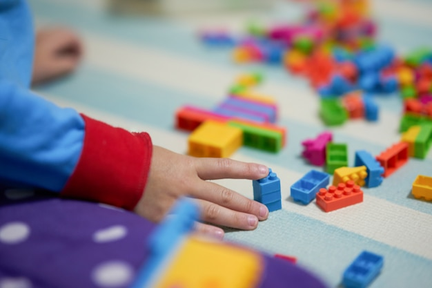 Kid hand touch colorful bricks toy on mat floor for playing Premium Photo