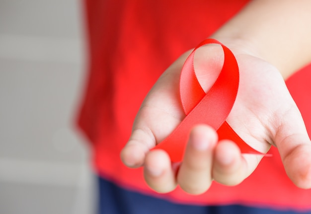 Kid hands holding red aids awareness ribbon. aids awareness campaign Premium Photo