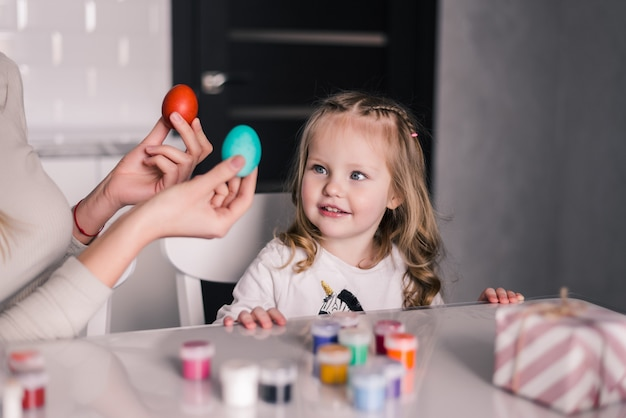 Kid having fun while painting easter eggs in the kitchen Free Photo