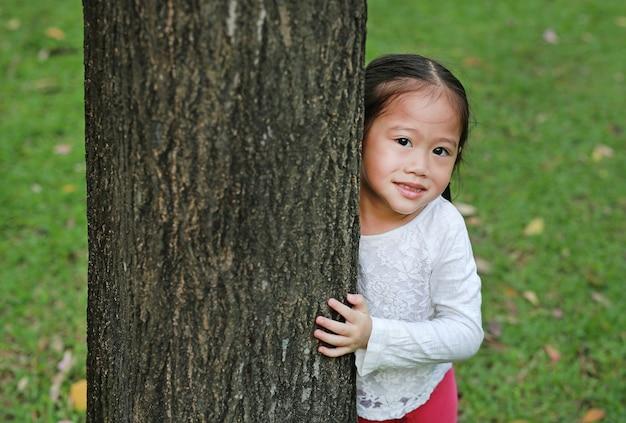 Kid hide body behind trunk Premium Photo