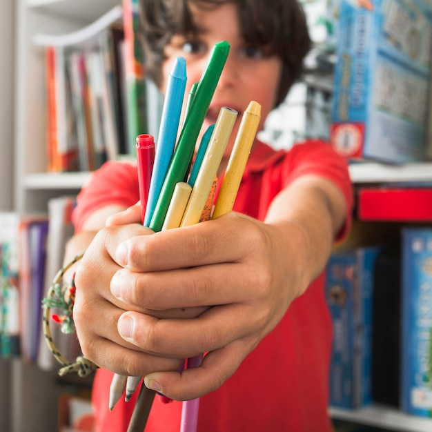 Kid holding drawing pencils Free Photo