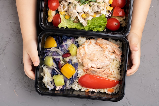 Kid holding lunch boxes with food ready to go for work or school, top view Premium Photo