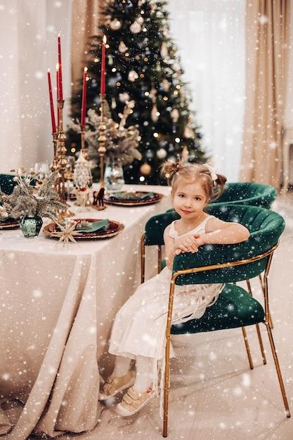 테이블 앞에 녹색 의자에 편안 해지는 드레스에 아이 무료 사진