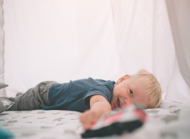 子供は床に横たわっています。少年は午前中自宅でおもちゃの車で家で遊んでいます。寝室でのカジュアルなライフスタイル。 Premium写真