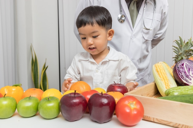 Kid learning about nutrition with doctor to choose eating fresh fruits and vegetables. Premium Photo