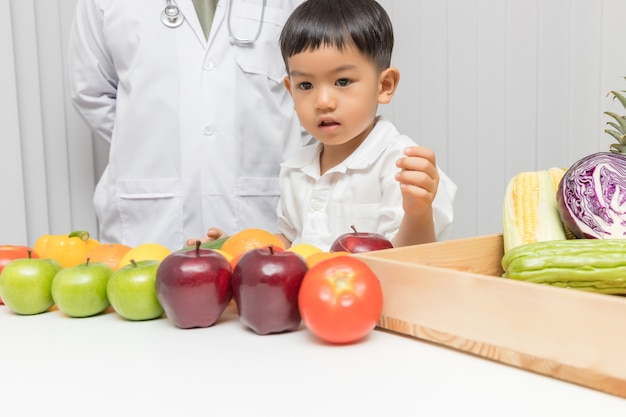 Kid learning about nutrition with doctor to choose how to eat fresh fruits and vegetables. Premium Photo