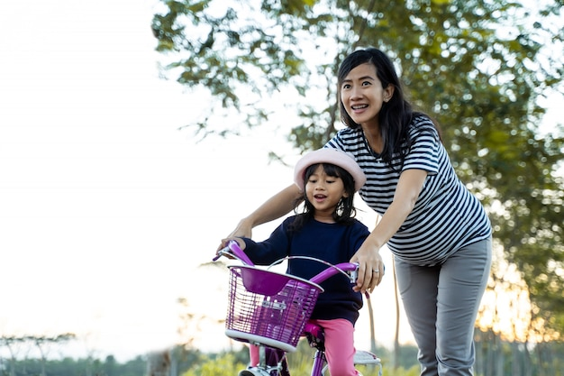 Kid learning to ride bicycle with mother Premium Photo