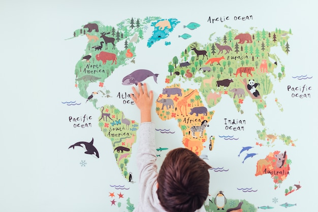Kid looking at world map Free Photo
