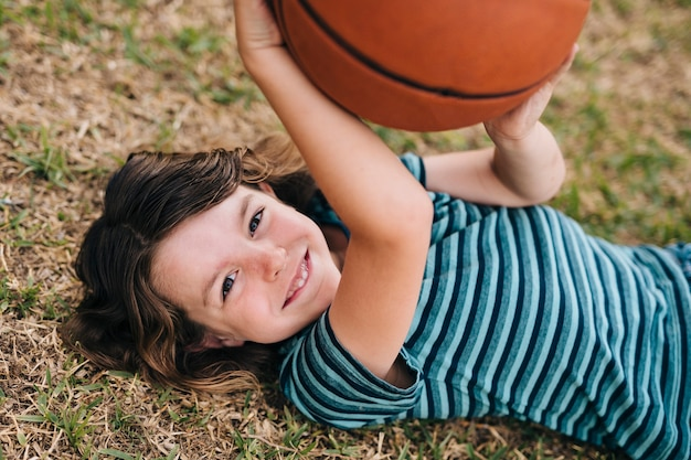Kid lying on grass and holding ball Free Photo