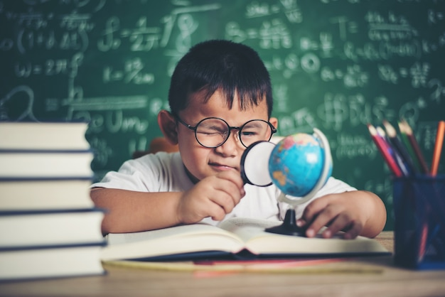Kid observing or studying educational globe model in the classroom. Free Photo