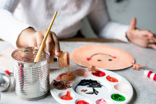 Kid painting santa on a paper plate Free Photo