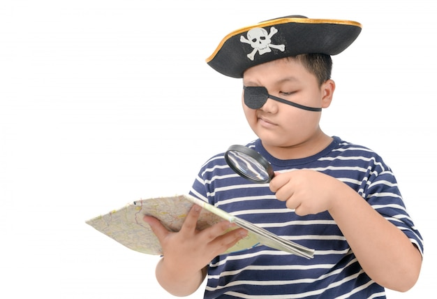 Kid pirate using magnifying glass to view the map Premium Photo