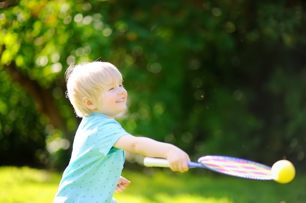 Kid playing badminton in summer park Premium Photo