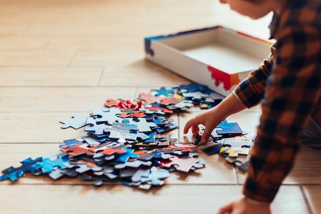 Kid playing with jigsaw Free Photo