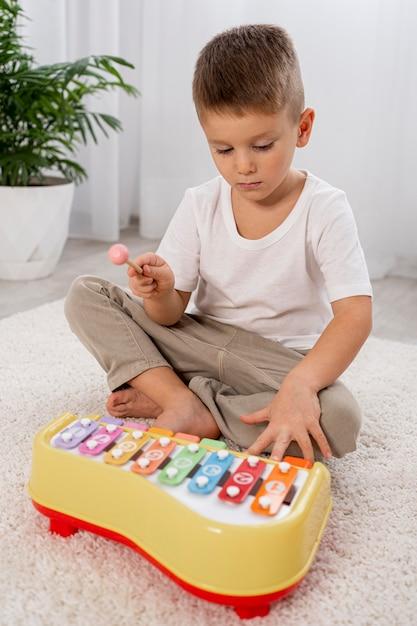 Bambino che gioca con un gioco musicale Foto Gratuite