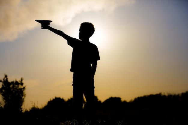 석양에 종이 비행기를 가지고 노는 아이 프리미엄 사진