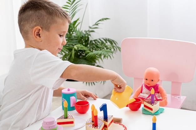 Bambino che gioca con un gioco del tè Foto Gratuite