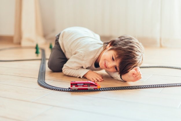Kid playing with toy train Free Photo