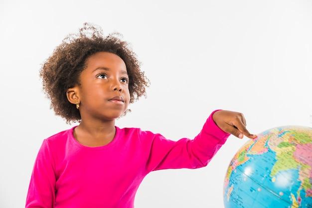 Kid pointing at globe in studio Free Photo