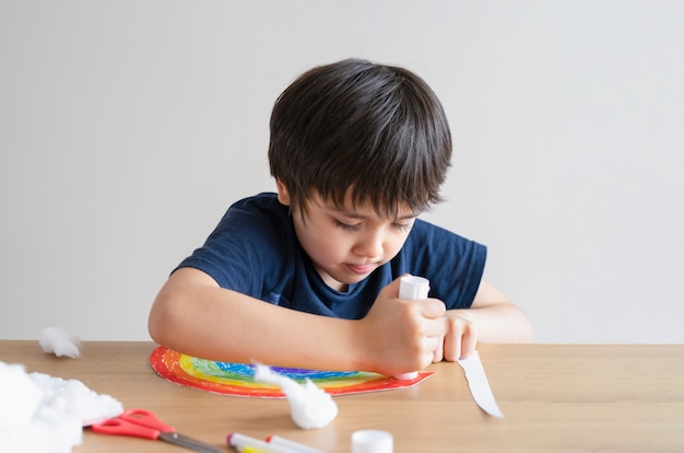 虹の雲の装飾的な要素として綿を貼り付けるために紙に接着剤棒を置く子供 Premium写真